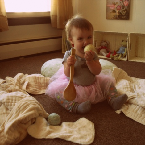 Fae, playing with cloth diaper laundry. You can see some of her baskets in the background.