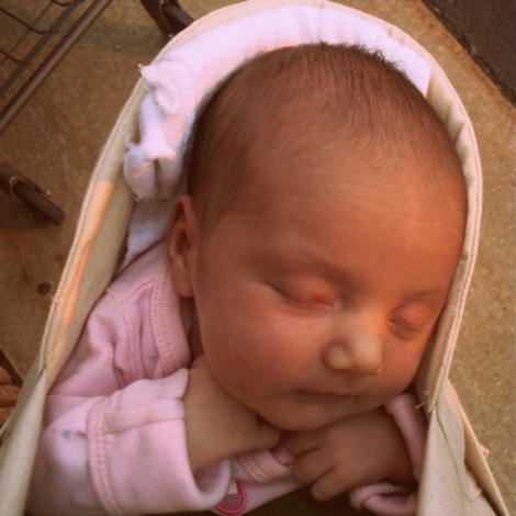 Fae, as a newborn, outside of the grocery store in the mei tai carrier.