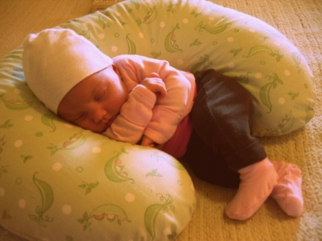 Napping on the Boppy pillow in a cozy cotton outfit.